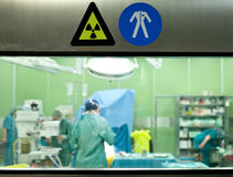 Warning signs busy surgery. Warning signs on door of operative room with busy doctors Stock Photography