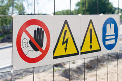 Warning signs on fence at construction site. Closeup Stock Images