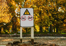 Warning Signs prohibiting bathing and dog walking. Warning notice : swimming and walking dogs banned. a fountain and a swimming pool without water outdoor autumn Stock Photography