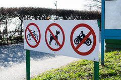 Warning Signs prohibiting bike, motorcycle and dog walking.  Royalty Free Stock Photos