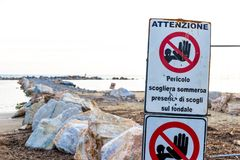Warning signs on the shoreline in Follonica, Italy. Warning signs reading: `Warning. Danger submerged reef, rocks on the shoal are present` near a construction stock photo