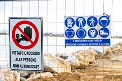 Warning signs on the shoreline in Follonica, Italy. Warning signs reading: `no entry unauthorised personnel` and `protective equipment must be worn` near a stock images