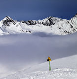 Warning sing on off-piste slope and mountains in fog Royalty Free Stock Image