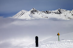 Warning sing, snowboard on off-piste and mountains in fog Royalty Free Stock Photo