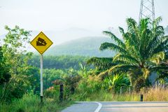 Warning Slope Sign Beside the Road, Yellow Sign to Attention for Downhill Road.  stock images