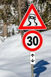 Warning and Speed Limit Signs on a Road Covered in Snow Stock Photos