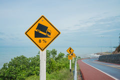 Warning steep road sign slope and truck on hill. And seaside stock image