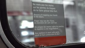 Warning sticker in moving metro train, Paris. Paris, France - September 29, 2017: Multilanguage warning poster on the window of moving subway train. Beware of stock footage