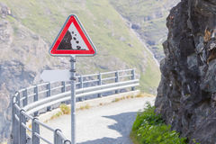 Warning stone fall road sign on mountain road Royalty Free Stock Photos
