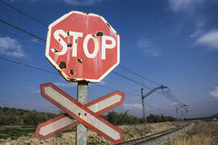 Warning stop sign worn of level crossing without barriers Stock Images