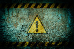 Warning symbol on dirty wall background with grunge and vignette Stock Image