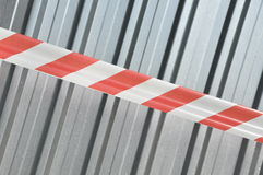 Warning tape with corrugated sheet metal Stock Photo