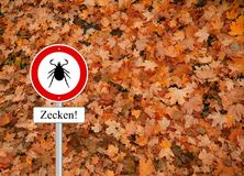 Warning tick sign autumn Stock Image