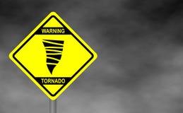 Warning tornado road sign . Yellow hazard warning sign against grey sky -  Stock Image