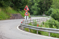 Warning traffic sign on metal pole on winding road Royalty Free Stock Photos
