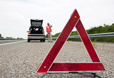 Warning triangle. Road side warning triangle, warning oncoming traffic of a broken down car, with a man using his cell phone to call for assistance Stock Photos