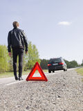 Warning triangle. In front of a car breakdown and a man walking stock photos