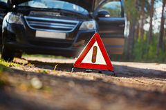 Warning triangle behind a broken down car. Focus on red triangle Royalty Free Stock Photos