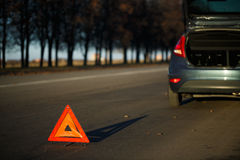 Warning triangle with a broken down car Stock Photos