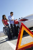 Warning Triangle With Couple Pouring Fuel Into Car Royalty Free Stock Photo