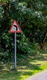 Typical British Roadway sign seen near a sharp bend, known for accidents. The warning triangle signified to road users of a sharp, left hand ben which is also a royalty free stock photography