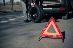 Warning triangle stands on the tarmac road. And man holds the spare tire on the background royalty free stock photo