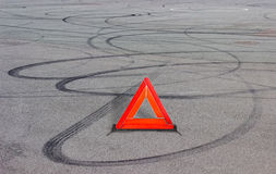 Warning triangle and tire tracks on asphalt Royalty Free Stock Photo