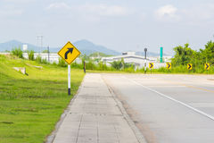 Warning turn right sign near the road. Rural road with yellow turn right warning sign stock image