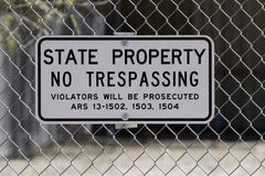 No Trespassing Sign along the I-10 in Phoenix. Warning, white and black no trespassing sign on chain link barrier fence along the I-10 freeway in downtown Royalty Free Stock Images