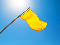 Warning yellow flag under sun with blue sky Stock Photography