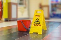 Warning yellow plastic sign of wet floor Stock Photo
