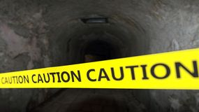 Warning yellow tape. With tunnel as background royalty free stock images