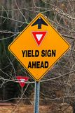 A warning Yield Sign Ahead sign in the fall.  stock photo