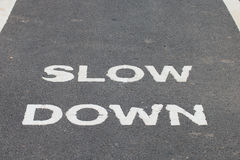 A warnning sign SLOW DOWN painted on the bike lane Stock Photography
