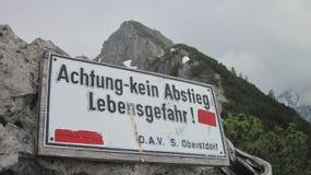 Warnschild in den deutschen Alpen für die Wanderer, Deutschland Stockbilder