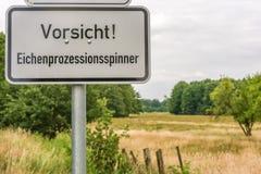 Warnschild mit dem deutschen Wort für Eichenprozessionsspinner vor schöner Landschaft stockfotos