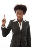 Warnung: Afrikanerin im Anzug, der den Finger lokalisiert anhebt lizenzfreie stockbilder