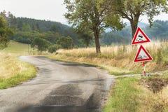 Warnzeichen der Straße auf glatter Straße Verschütteter Kies auf der Straße Land-Straße in der Tschechischen Republik Lizenzfreie Stockfotografie