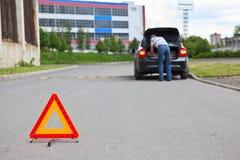 Warnzeichen des Dreiecks auf Straße mit Treiber im Auto Lizenzfreie Stockfotos