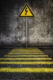 Warnzeichen des gelben Stroms an der Schmutzwand vor Fußgängerübergang Lizenzfreie Stockfotos