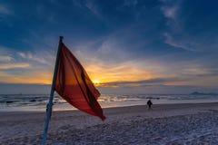 Warnzeichen einer roten Fahne auf dem Sonnenaufgang a des Strandes morgens Lizenzfreies Stockbild