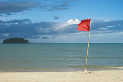 Warnzeichen einer roten Fahne an einem schönen sauberen Strand mit einem blauen Himmel, Wolke und dem Meer mit kleiner grüner Ins Lizenzfreies Stockbild