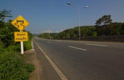 Warnzeichen für glatte Straße voran Stockbilder