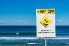 Warnzeichen mit Strand auf dem Hintergrund Stockfotos