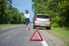 Warnzeichen und Frau des roten Dreiecks nahe defektem Auto stockbild