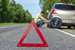 Warnzeichen und Mann des roten Dreiecks, die den Reifen ändert lizenzfreie stockfotos