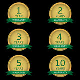 Warranty label set. Golden guarantee badges with green ribbons Royalty Free Stock Image