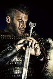 Warrior. Portrait of a courageous ancient warrior in armor with sword Royalty Free Stock Image