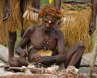 Warrior Asmat tribe sits and carves a ritual statue. INDONESIA, IRIAN JAYA, ASMAT PROVINCE, JOW VILLAGE - JANUARY 19: Warrior Asmat tribe sits and carves a Stock Photos