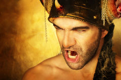 Warrior cry. Sexy powerful warrior screaming against golden background Stock Photography